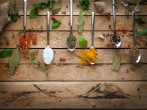 Spices and herbs in spoons on wooden background, top view royalty free stock photos