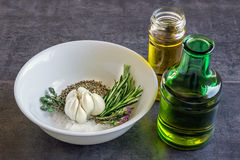 Spices and herbs in a white bowl, next to bottles of olive oil Royalty Free Stock Photos