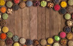 Spices and herbs on wooden table background. Frame of colorful seasonings, top view. Indian spices and herbs on wooden table.Condiment collection with empty stock photography