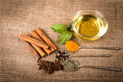 Spices, herds and oil on a burlap Royalty Free Stock Photography