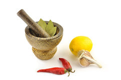 Spices, lemon  and a mortar on a white background Royalty Free Stock Photos