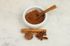 Spices on marble. Chinese five spice with cinnamon, nutmeg and star anise on a marble worktop royalty free stock images