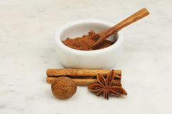 Spices on marble. Chinese five spice in a ramekin with nutmeg, star anise and cinnamon on a marble worktop stock photos