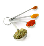 Spices in measuring spoons. Assorted spices in metal measuring spoons on white background Stock Image