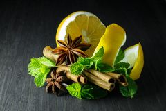 Spices; mint, star anise, cinnamon, lemon on a dark tree stock photography