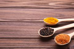 Spices mix in spoon on a brown wooden background. Top view royalty free stock photo