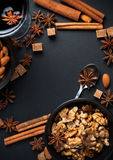 Spices for mulled wine. Cinnamon, star anise, brown sugar, red wine and nuts on a black background in studio Royalty Free Stock Photo
