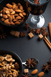 Spices for mulled wine. Cinnamon, star anise, brown sugar, red wine and nuts on a black background in studio Stock Photo