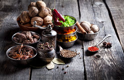 Spices and nuts at wooden table Stock Images