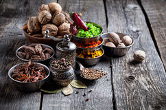 Spices and nuts at wooden table Stock Photography