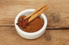 Spices on old wood. Chinese five spice in a ramekin with a cinnamon stick and star anise on old weathered wood royalty free stock image