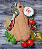 Spices, olive oil, tomatoes and wooden board Stock Image