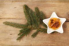 Spices, orange and pine needles. Dried orange, cinnamon, star anise and cloves in a star shaped dish with pine needles on old rustic wood royalty free stock photos