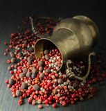 Spices; pepper white, pink, black, scented, brass jug on dark background royalty free stock photos