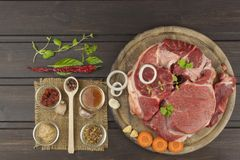 Spices and raw beef shank on the cutting board. Preparing spicy food. Decorations for the menu. Beef ready for cooking Royalty Free Stock Images