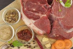 Spices and raw beef shank on the cutting board. Preparing spicy food. Decorations for the menu. Stock Image