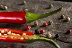 Spices: red hot chilli pepper with colored peppercorns. On rustic wood background Royalty Free Stock Photography