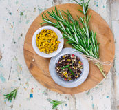 Spices, rosemary and pepper on wooden board Stock Photo