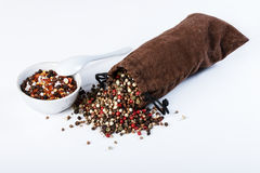 Spices in a sack, bulk spices in a porcelain dish, spoon on a wh Stock Image