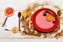 Spices scattered all over wooden surface. Plate and spoons with dried orange and chilly pepper on white wooden. Background. Spices as grinded red pepper and stock photo