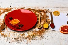 Spices scattered all over wooden surface. Spices as grinded red pepper and curcuma powder scattered. Culinary concept. Plate and spoons with dried orange and royalty free stock photos