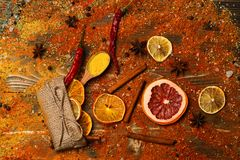 Spices scattered all over wooden surface. Spoons filled with cinnamon, grinded red pepper and curcuma powder and kitchen. Herbs scattered on table. Spoons with royalty free stock images