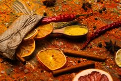 Spices scattered all over wooden surface. Spoons filled with cinnamon, grinded red pepper and curcuma powder and kitchen. Herbs scattered on table. Spices stock photos