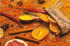 Spices scattered all over wooden surface. Spoons filled with cinnamon, grinded red pepper and curcuma powder and kitchen. Herbs scattered on table. Spices royalty free stock photos