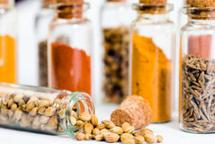 Spices series. A few bottles of spices in a jar with one of the jar spilled on the surface Royalty Free Stock Photo