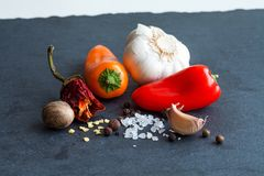 Spices set on the black rock board. Bell pepper seeds dried chili black, nutmeg sea salt and garlic. Macro view Stock Photo