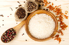 Spices on spoon and in pouches, rice in wooden bowl on  a wooden table background. Rice in a wooden bowl and spices on a wooden surface Stock Image