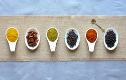 Spices in the spoons over a black stone. Table Royalty Free Stock Photos