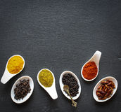 Spices in the spoons over a black stone. Table Stock Photography