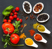 Spices in the spoons over a black stone. Table Royalty Free Stock Photo