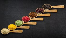 Spices in spoons over black table background. Top view of season. Indian spices in spoons on table background, top view stock image