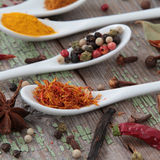 Spices in the spoons. On the wooden background Royalty Free Stock Images