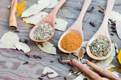 Spices in spoons on wooden table Stock Photo