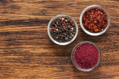Spices of sumac, pepper and dried tomatoes in glass cups on a wooden background. Royalty Free Stock Photos