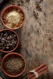 Spices in three ceramic bowls on the wooden background, close-up, selective focus, vertical. Spices in three ceramic bowls on the wooden background, close-up Stock Photography