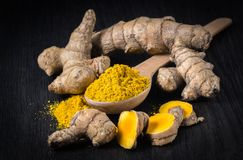 Spices; turmeric, root, cut, grated on dark background stock photos