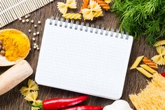 Spices and vegetables around notebook Stock Images