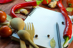 Spices, vegetables, and a notebook Stock Images
