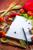 Spices, vegetables, and a notebook Stock Photography
