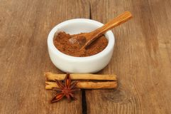 Spices on weathered wood. Chinese five spice in a ramekin with cinnamon and star anise on old weathered wood stock image