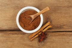 Spices on wood. Chinese five spice in a ramekin with cinnamon and star anise on weathered wood royalty free stock images