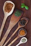 Spices and wood. Spices on wooden spoons on wooden background Royalty Free Stock Images