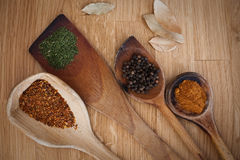 Spices and wood. Spices on wooden spoons on wooden background Royalty Free Stock Image