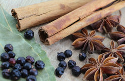 Spices on a wooden chopping board. A composition with some star anise, some juniper berries, cinnamon sticks and laurel leaves on a wooden chopping board Stock Image