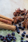 Spices on a wooden chopping board. A composition with some star anise, some juniper berries, cinnamon sticks and laurel on a wooden chopping board, portrait cut Royalty Free Stock Photos