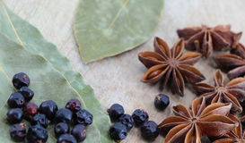 Spices on a wooden chopping board. A composition with some star anise, some juniper berries and some laurel leaves on a wooden chopping board, landscape cut Royalty Free Stock Photos